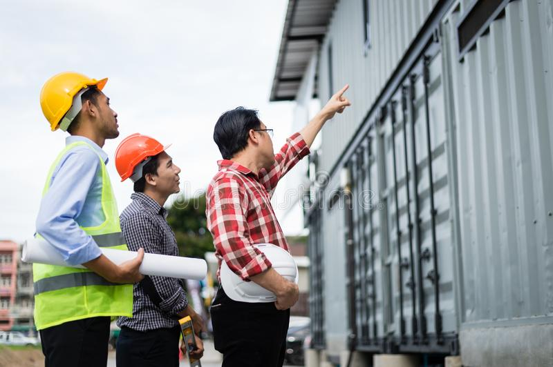 Foreman and employee holding blueprint on hand and pointing finger to building. engineer checking construction process royalty free stock photography