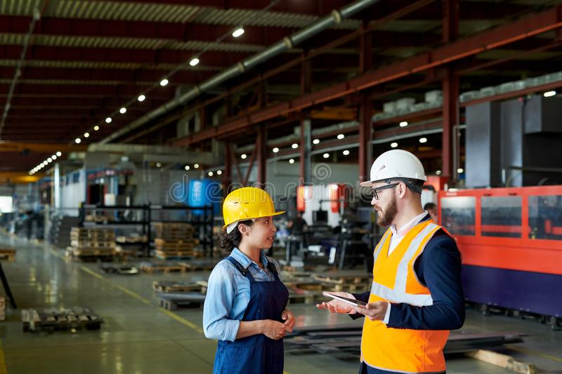 Foreman Instructing Worker at Plant. Side view portrait of production manager wearing hardhat talking to female factory worker standing in production workshop royalty free stock photos