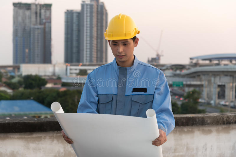 Foreman looking at blueprint at a construction site stock photography
