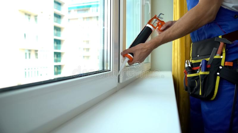 Foreman repairing window sealing frame to provide sound insulation, installation. Stock photo stock image