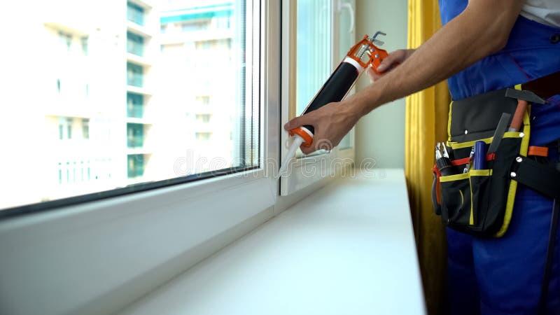 Foreman reparando moldura de vedação de janelas para fornecer isolamento de som, instalação imagem de stock