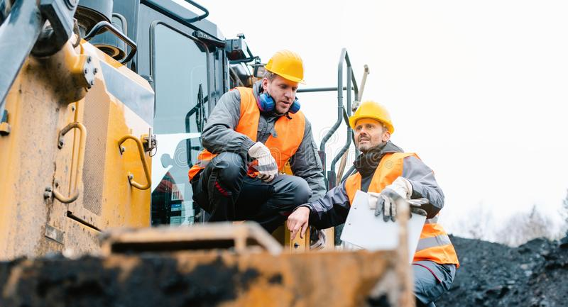 Foreman showing worker in open-cast mining pit direction royalty free stock photos