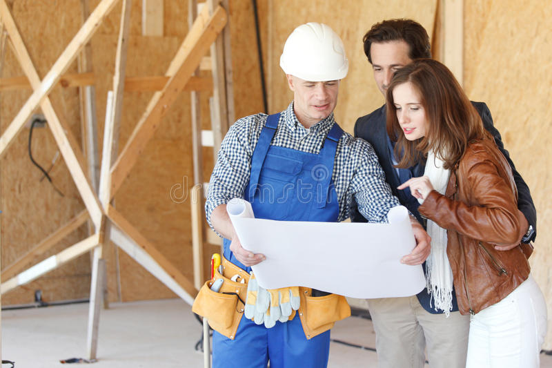 Foreman shows house plans to couple royalty free stock photos
