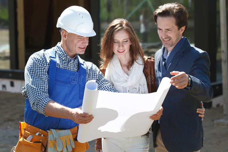 Foreman shows house plans to couple stock photo