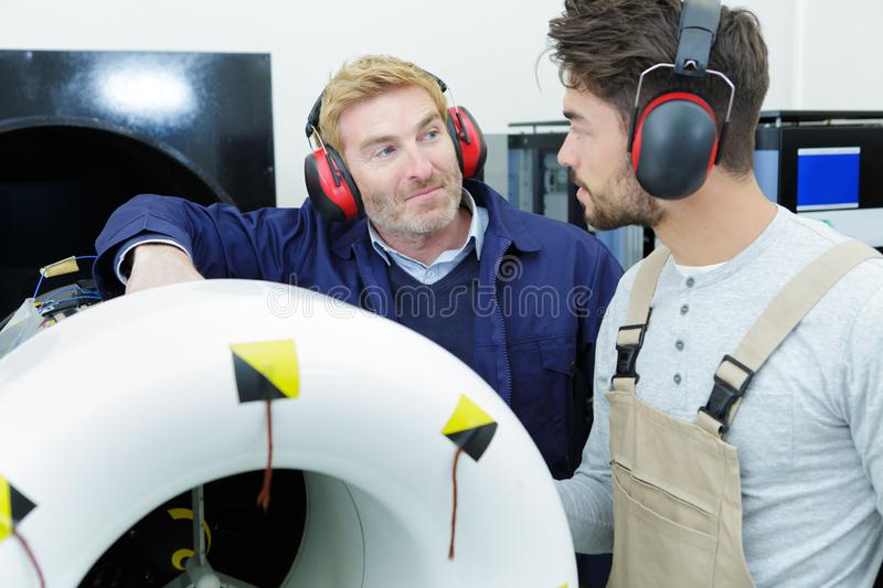 Foreman teaching apprentice engineer stock photography