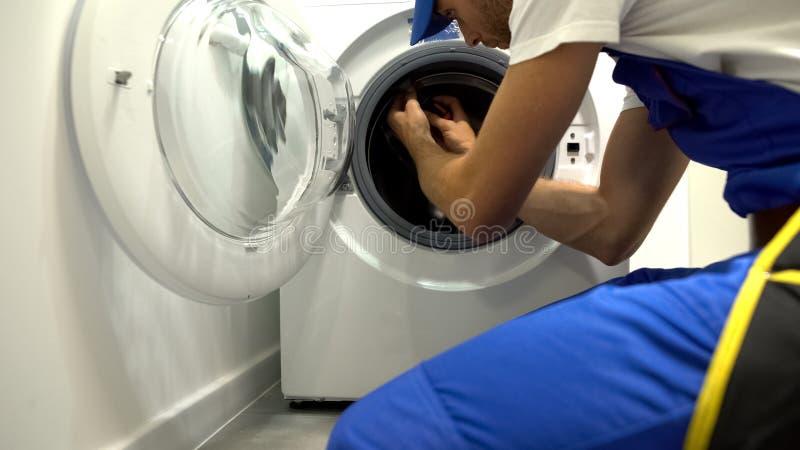 Foreman in uniform repairing washing machine using screwdriver, maintenance royalty free stock photos