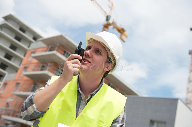 Foreman using walkie-talkie and yell on construction site royalty free stock photos