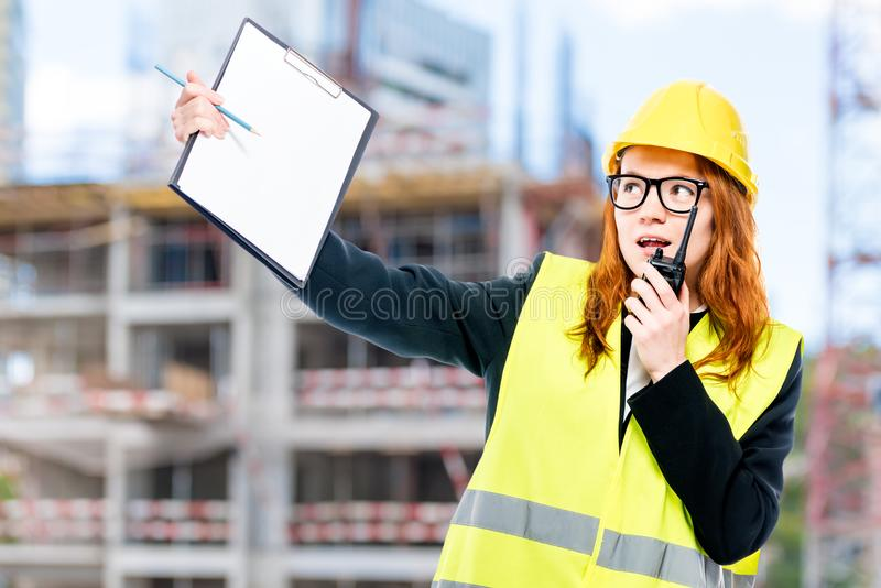 Foreman with a walkie-talkie in a vest and a yellow helmet again. St the background of the building under construction royalty free stock photos