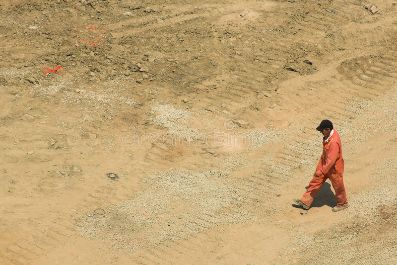 Foreman walks through construction site royalty free stock image