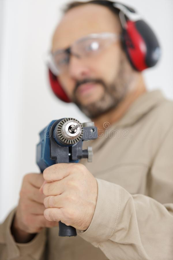 Foreman wearing helmet drilling wal by drill. Man stock photos