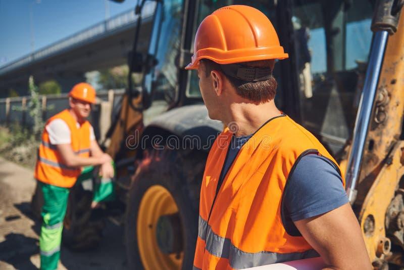 Foremans i orange västar är att arbeta som är utomhus- royaltyfri bild