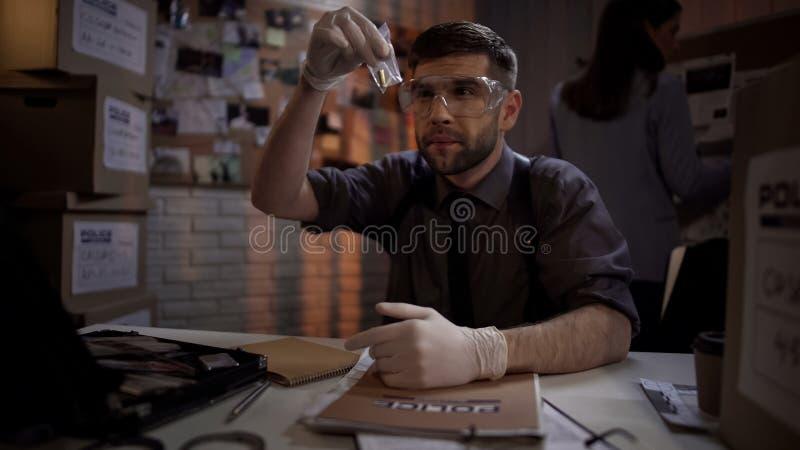 Forense atractivo que trabaja con la bala, pruebas en el Departamento de Policía imágenes de archivo libres de regalías