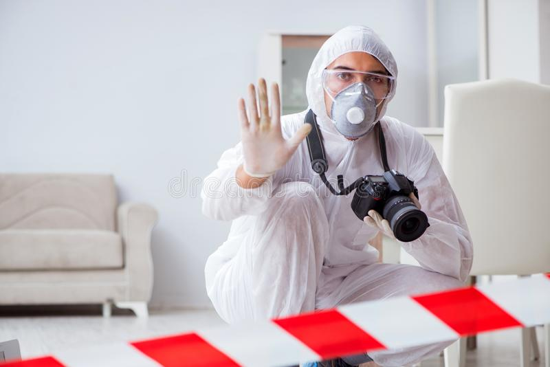 The forensic expert at crime scene doing investigation. Forensic expert at crime scene doing investigation stock image