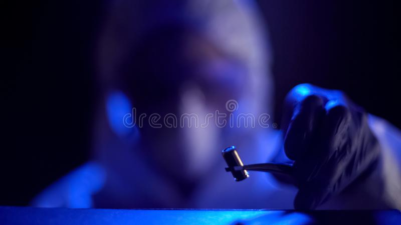 Forensic expert taking bullet at crime scene, personal investigation, night time. Stock photo royalty free stock image