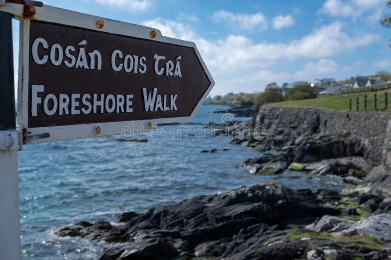A foreshore walk sign in English and Irish, pointing to the walk along the jagged cliff with the Atlantic ocean crashing on the. Rocks against a bright blue sky royalty free stock image