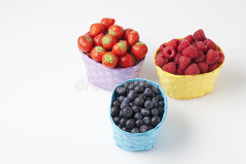 Forest berries, raspberries, blueberries and strawberries in baskets stock images