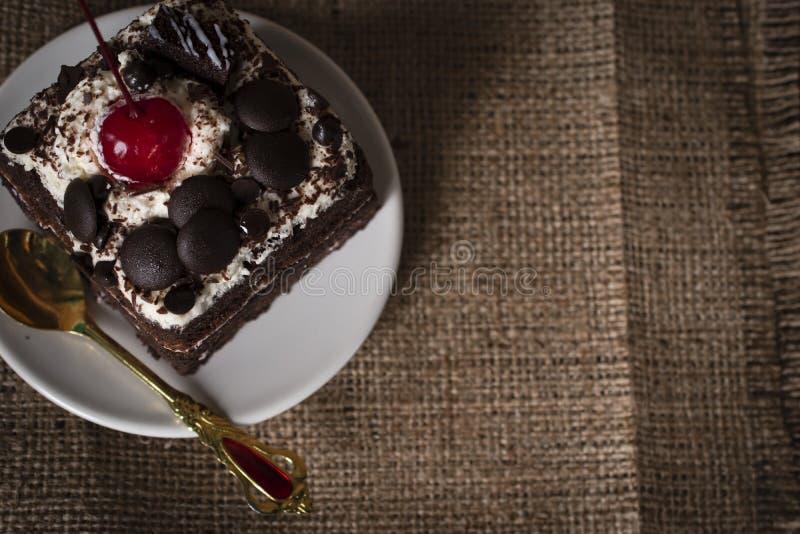 Forest Cake noir complétant la mise oblique d'or de couleur de cerise, de chocolat et de cuillère sur le plat blanc photographie stock libre de droits