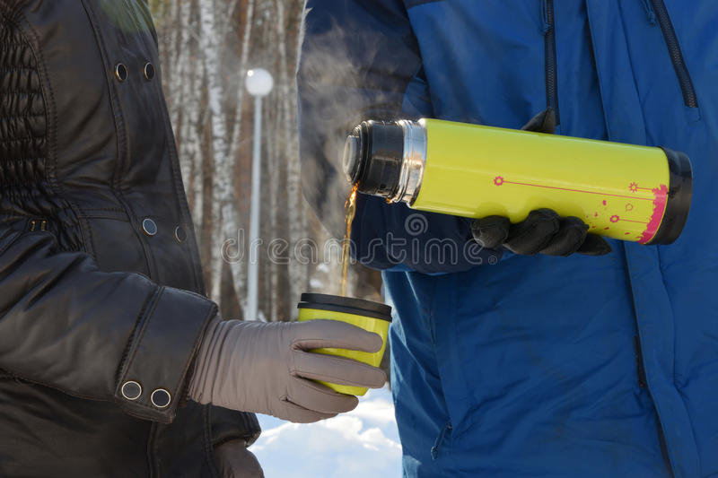 In the forest, in the cold, a man pours a woman hot tea from a thermos. In the forest, in the cold, a man pours a woman hot tea from a yellow thermos stock images