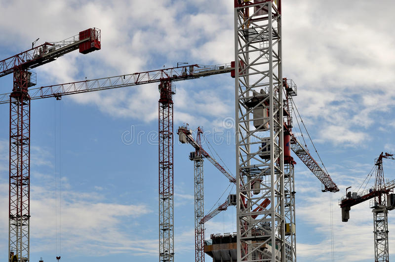 Forest of cranes, milan. Foreshortening of many cranes in a big construction site in city center, shot from the street under cloudy sky royalty free stock photos
