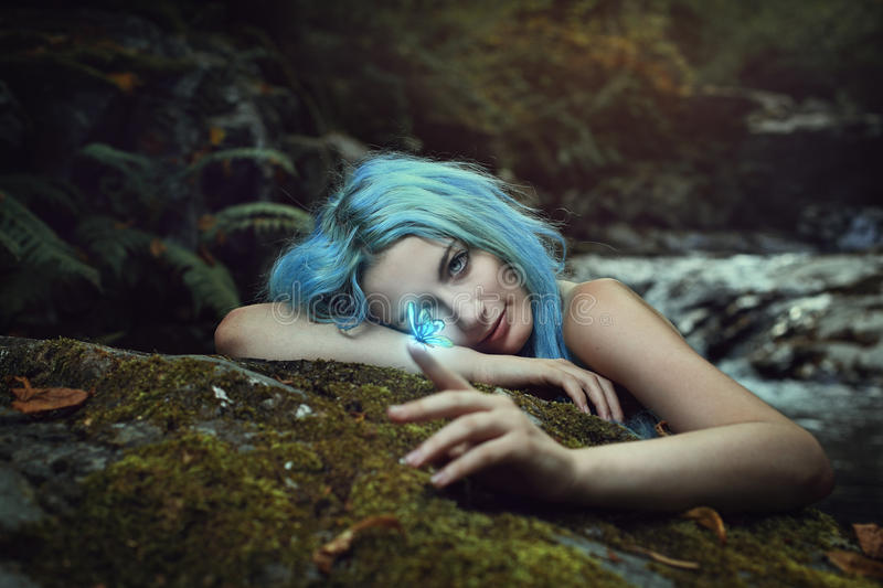 Forest dryad observing a magical butterfly stock images