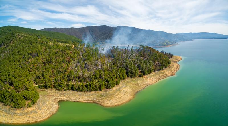 Forest fire on shores of Blowering Reservoir. royalty free stock photography