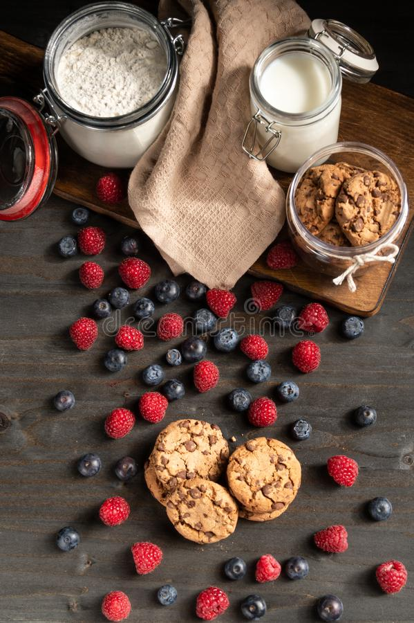 Forest fruits, homemade cookies, milk and flour table top. royalty free stock photography