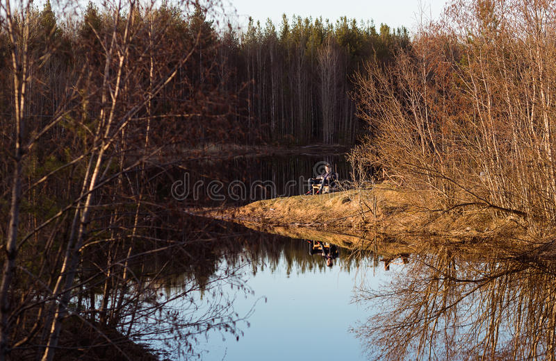 Forest lake landscape with man relaxing on chair.  stock photo