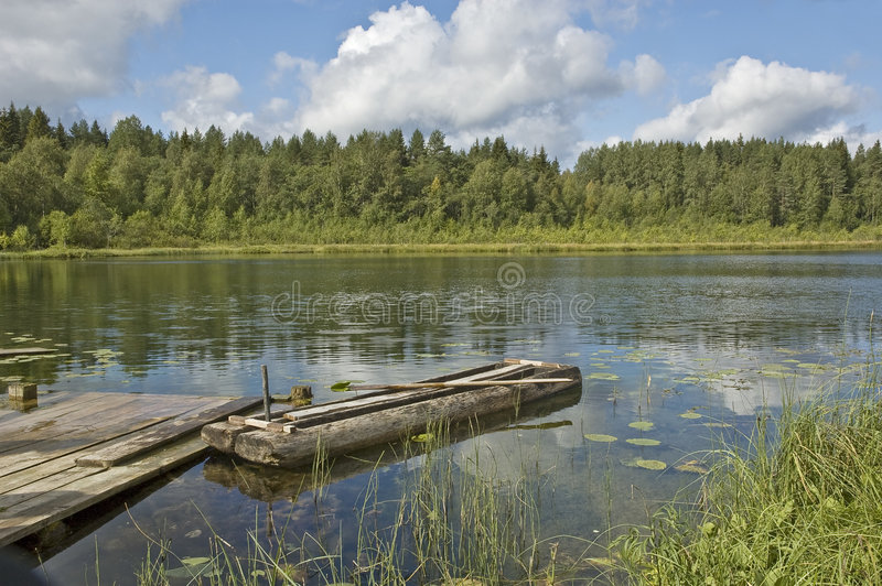 Forest lake with old wooden boat. Little forest lake with old traditional wooden boat, near Kargopol, north Russia stock image