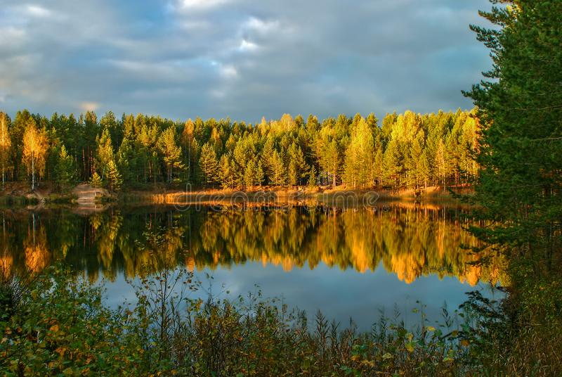 The forest lake at sunset, with reflection of sky and forest on a water smooth surface stock image