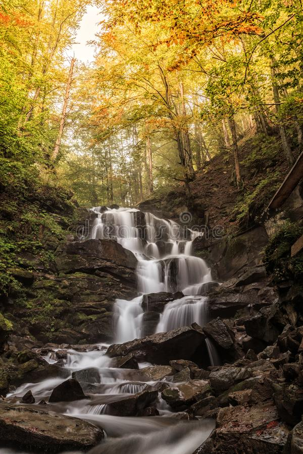Forest landscape with a beautiful waterfall on a mountain river creek Cascades autumn beech forest Carpathians, Ukraine, Europe royalty free stock photo