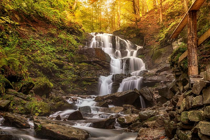 Forest landscape with a beautiful waterfall on a mountain river creek Cascades autumn beech forest Carpathians, Ukraine, Europe. Forest landscape with a royalty free stock image
