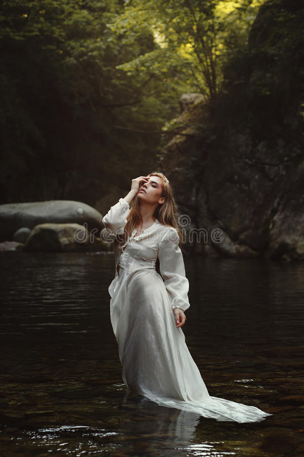 Forest maiden in mystical waters. Young forest maiden in mystical waters. Dark woods stock images