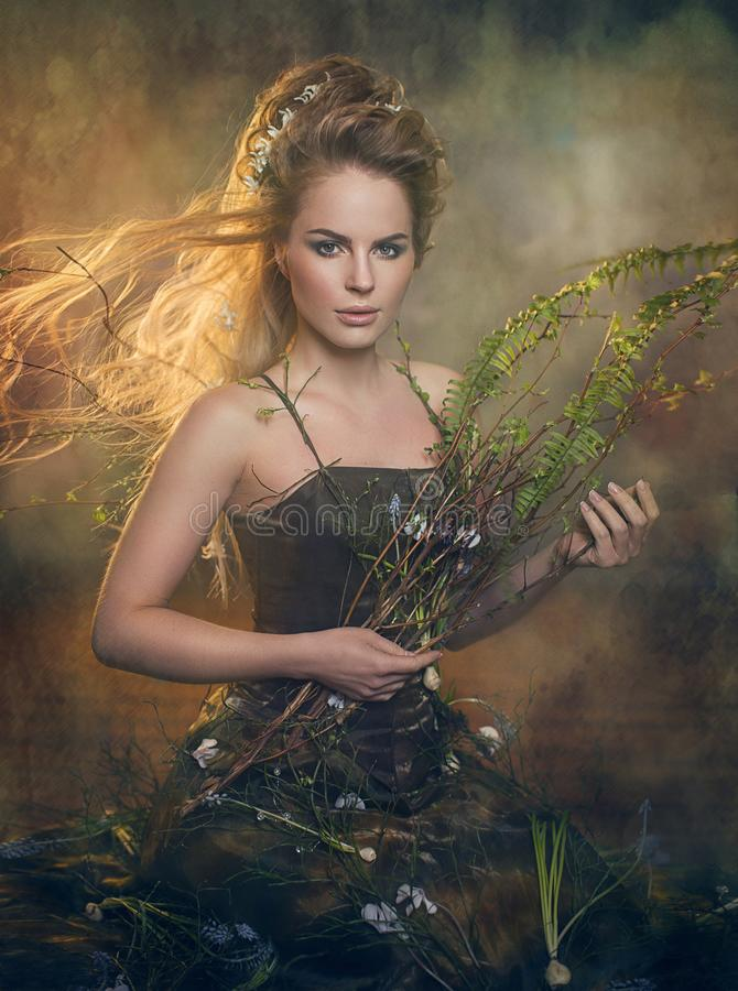 Forest nymph with long hair. Fabulous girl in green twigs and leaves on textured background in smoke stock photo