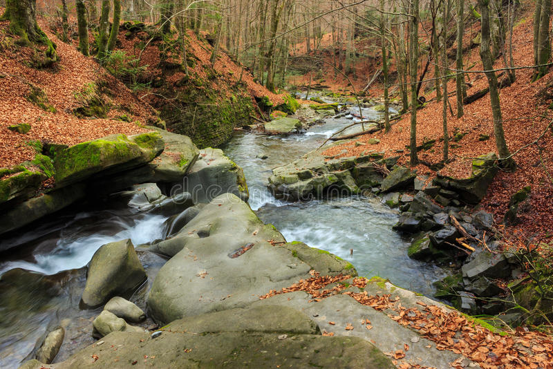 Forest river with stones and moss. Mountain river with stones and moss in the late autumn forest stock photos