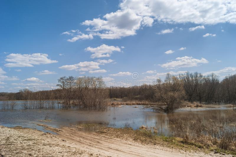 Forest road flooded by the spring flow of the river. Water landscape under a beautiful cloudy sunny sky. Road flooded by the spring flow of the river. Water stock photography