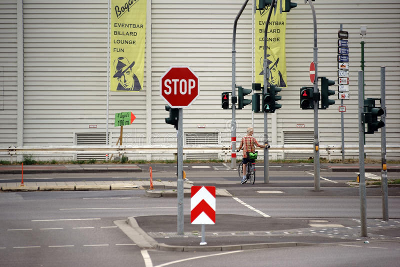 Forest of signs. Mainz, Germany - August 14, 2015: A cyclist stands at a red light intersection in front of a hardware store on a street with many traffic signs stock images