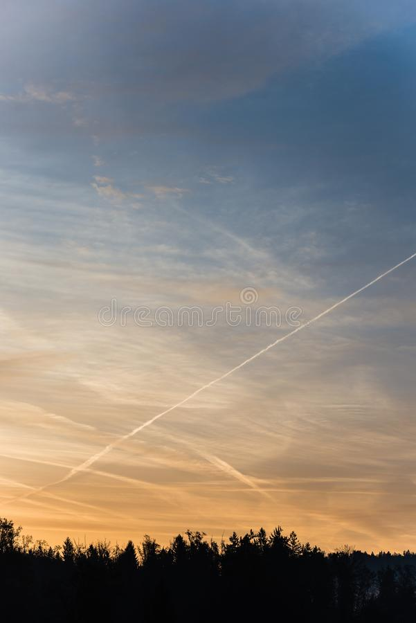 Forest silhouetted against contrails in colorful morning sky stock photography