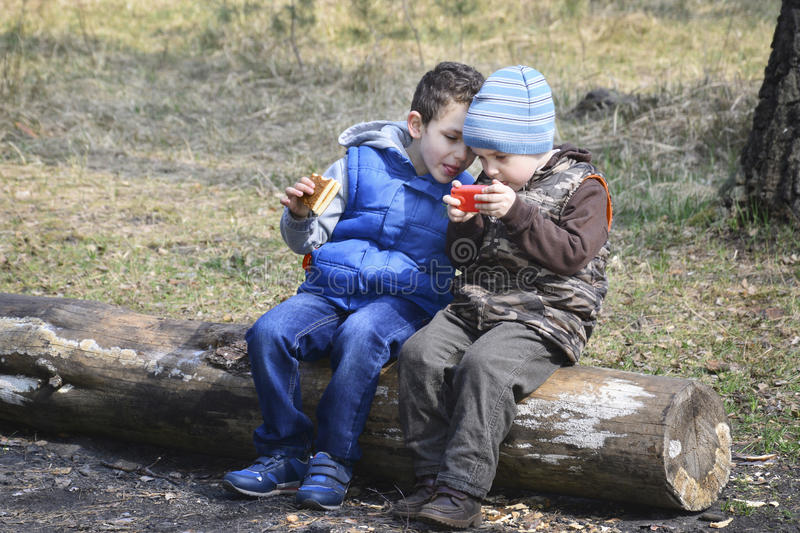 In the forest, sitting on a log, two boys, one playing with a to stock image