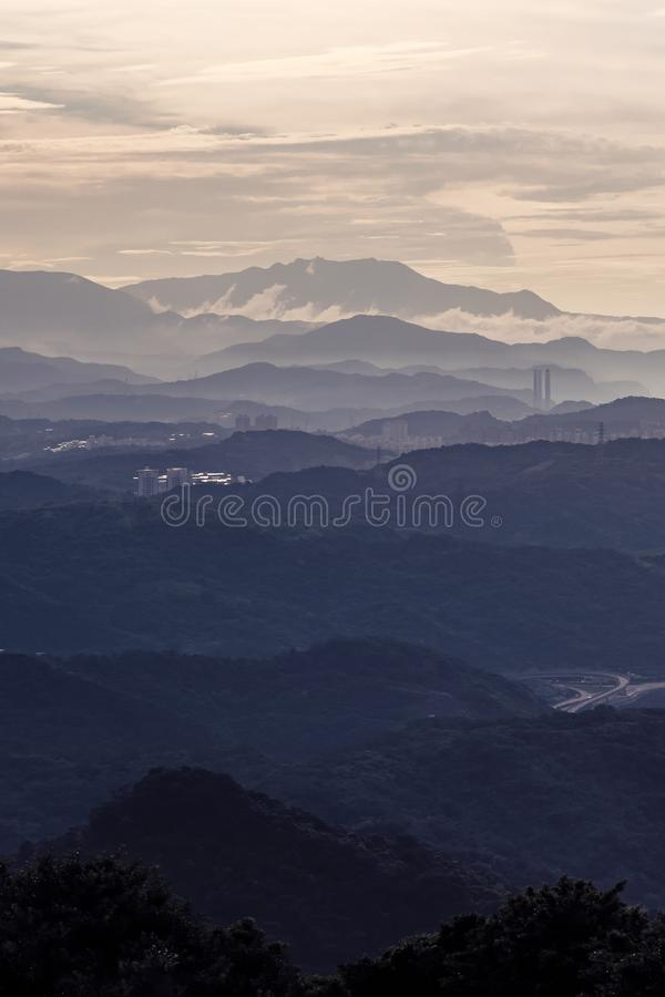 Forest trees and mountains range with visible silhouettes with fog and cloud sky at sunset in New Taipei City, Taiwan. Natural. Landscape stock photos