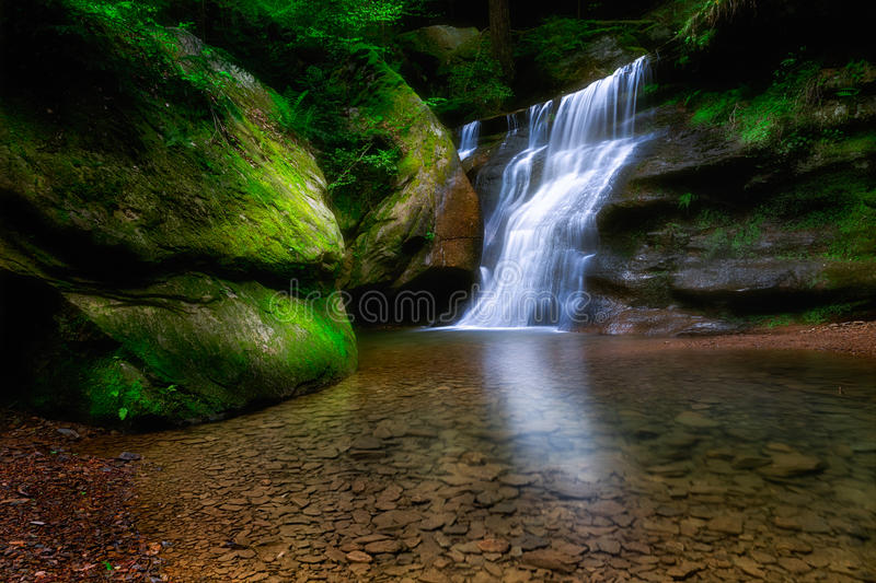 A forest waterfall over a small cliff. A small waterfall cascades over a cliff stock photography