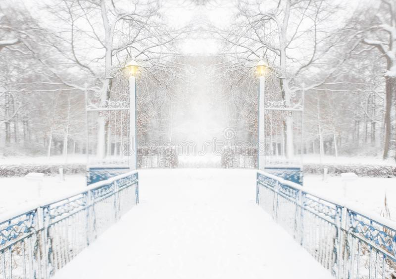 Forest in the winter with a blue bridge and lights on a snowy day. Forest in the winter with white snow and a bridge with lights with a winter landscape snowing stock photos