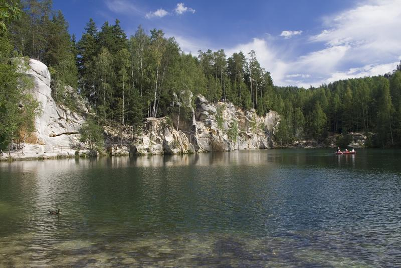 Foresta e massi dietro un lago immagine stock libera da diritti