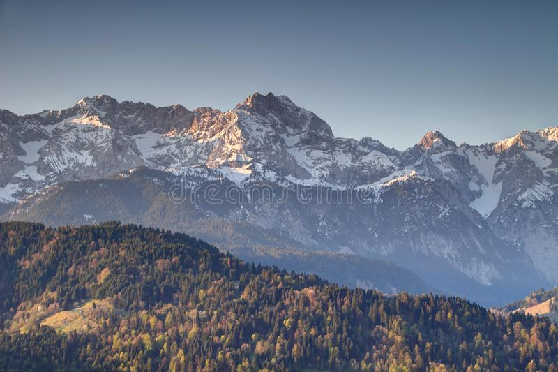Forested and snowy ridges of Wetterstein Bavaria Germany. Forested and snow covered ridges of Wettersteingebirge range with Schachen peak and triple summit of royalty free stock photo