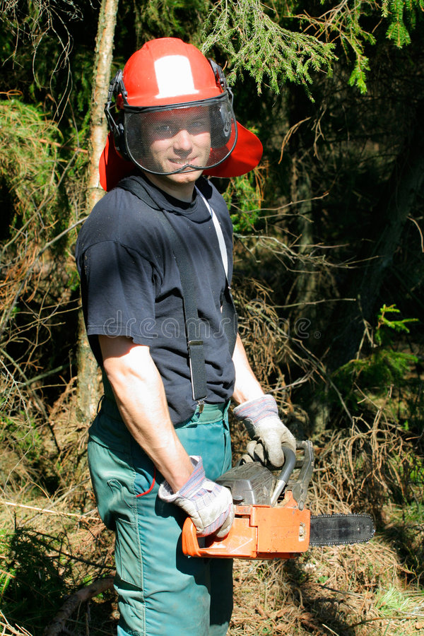 Forestry worker. A handsome smiling forestry worker in front of dense wood growth stock photos