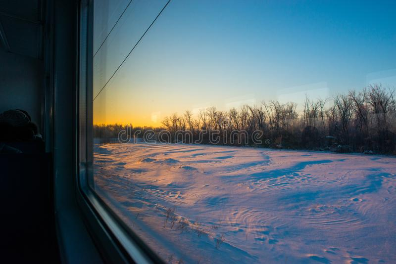 Forests and fields in the rays of dawn through the window of a speeding train stock photography