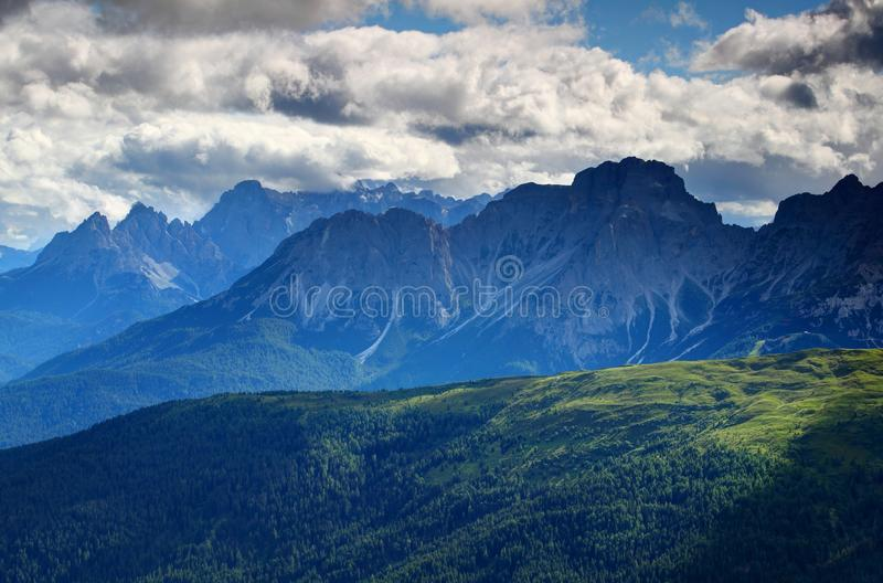 Forests, meadows and jagged peaks in blue mist Dolomites Italy. Forests, meadows in afternoon sunlight with jagged ridges in glowing blue mist and white cumulus royalty free stock photo