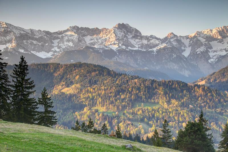 Forests, meadows and snowy ridges in Bavarian Alps Germany. Forests and steep snowy ridges of Wettersteingebirge range with Dreitorspitze and Schachen peaks from stock photos