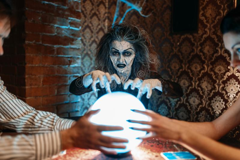 Foreteller calls the spirits over a crystal ball. Female foreteller calls the spirits over a crystal ball, witchcraft. Scary witch reads a magic spell, young stock photos
