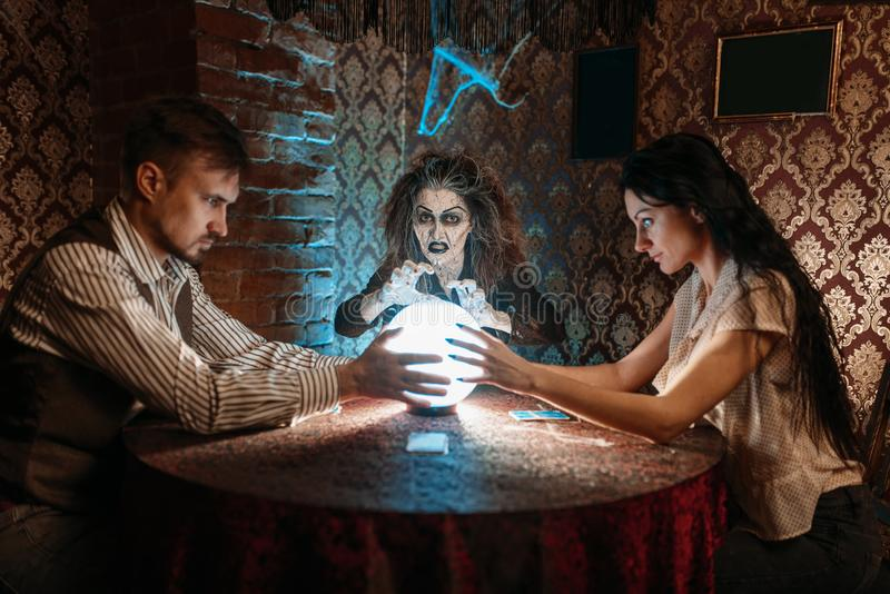 Foreteller calls the spirits over a crystal ball. Female foreteller calls the spirits over a crystal ball, witchcraft. Scary witch reads a magic spell, young stock image