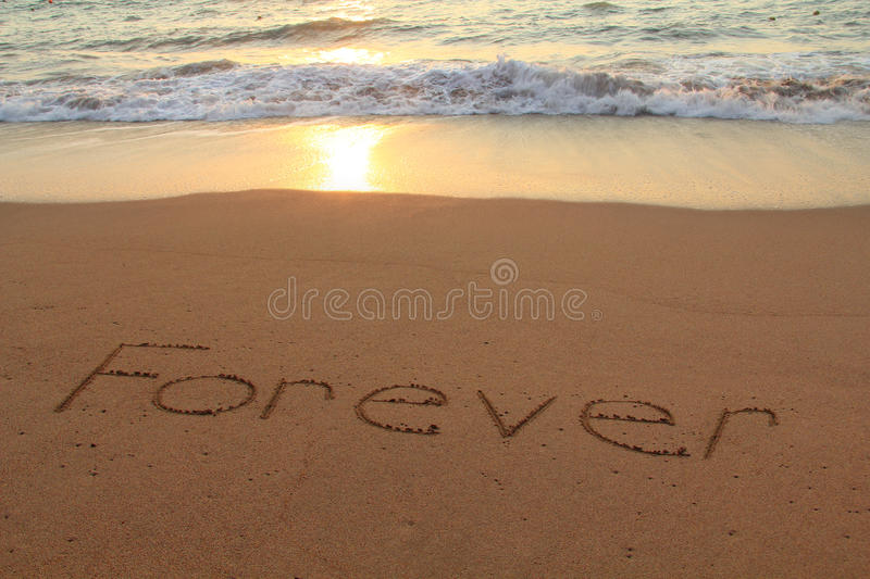 Forever beach. Forever written in the sand on a beach at sunset royalty free stock image